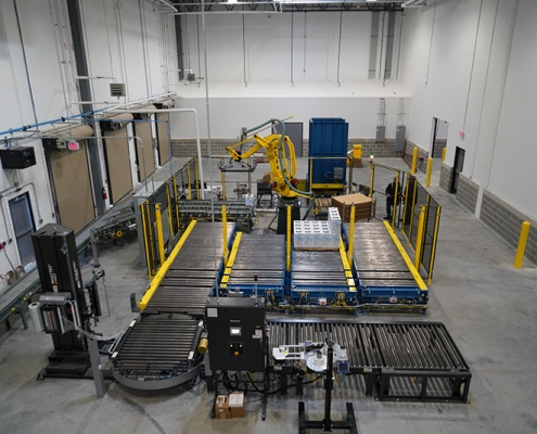 Robotic Carton Palletizing System including Fanuc M410iB/140H palletizing robot, Hytrol zero pressure accumulation conveyor infeed, Alba CDLR pallet conveyor and pallet dispenser with Wulftec WCA Smart stretch wrapper