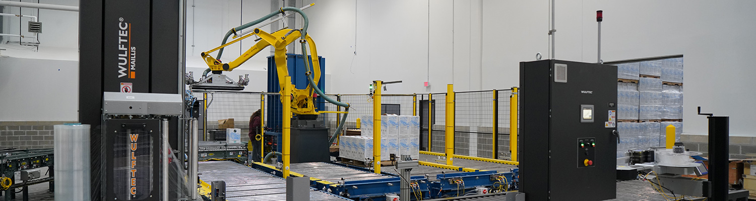 Robotic Palletizing System including Fanuc M410iB/140H palletizing robot with indeed from Hytrol EZ Logic 24 volt zero pressure accumulation conveyor and Hytrol 138 ACC powered accumulating roller conveyor. Alba pallet dispenser, Alba CDLR pallet conveyor and Alba 3 strand chain transfer conveyor used to send palletized load to Wulftec WCA Smart stretch wrapper.