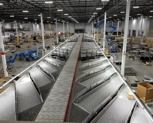 Intelligrated Shoe Sorter Conveyor leading into Chute System for high speed sortation system custom designed for a Global Parcel Shipping Company